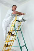 Painter climbing ladder to paint ceiling — Stock Photo