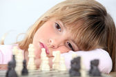 Bored girl playing chess — Stock Photo