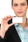 Smart woman holding a blank business card — Stock Photo