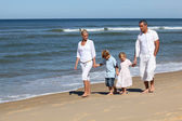 Family with children walking on the beach — Stock Photo