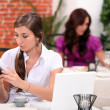 Woman receiving a text message in a restaurant — Stock Photo