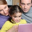 Parents and daughter sat with laptop — Stock Photo #9578681