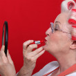 Woman with curlers putting on lipstick — Stock Photo