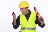 Irate builder shouting down phone — Stock Photo