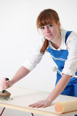 Female decorator with wallpaper — Stock Photo