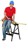 A carpenter seating on a workwrench. — Stock Photo