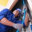 Plumber pulling tube - Stock Photo