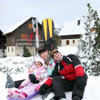 Stock Photo: Family of skiers sat by chalet