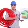 Stock Photo: Plumber holding faucet and energy consumption label