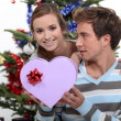 A boy giving a heart shaped box to a girl — Stock Photo