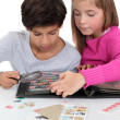 Children looking at a stamp album - Stock Photo