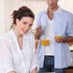 Couple drinking orange juice whilst using laptop — Stock Photo #9582447