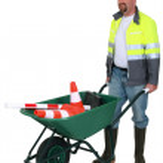 Workman pushing wheelbarrow, studio shot — Stock Photo