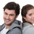 Portrait of a young man and woman standing back to back — Stock Photo