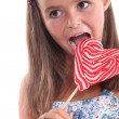 Stock Photo: Girl about to lick heart lollipop
