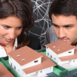 Two architect looking a miniature housing model — Stock Photo