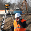 Surveyor at construction site - Stock Photo