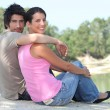 Couple sat by lake — Stock Photo
