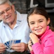 Stock Photo: Young girl playing cards with grandpa