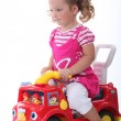 Little girl sat on toy truck — Stock Photo