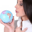 Woman blowing on a mini globe — Stock Photo #9585061