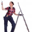 Woman with paint roller stood by ladder — Stock Photo