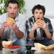 Father and son sat on the sofa eating burgers - Foto Stock