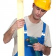 Young construction worker screwing a wooden plank — Stock Photo #9585488