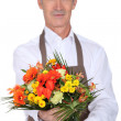 Stock Photo: Senior florist holding a bouquet