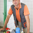 Stock Photo: Plumber leaning on his work-bench