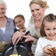 Three generations cooking pancakes - Stock Photo