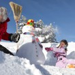 Little girl and grandfather making a snowman - Stockfoto