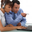 Stock Photo: Two office colleagues looking at a laptop