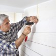 Grey-haired man replacing house paneling — Stock Photo #9586113