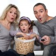 Parents with daughter watching TV and eating popcorn — Stok Fotoğraf #9587327