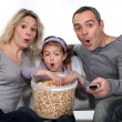Parents with daughter watching TV and eating popcorn — Stock Photo #9587327