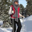Stock Photo: Woman walking through the snow with snow shoes