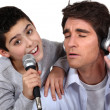 Man with headphones and little boy singing in a microphone — Stock Photo