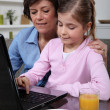 Mother and daughter sat at laptop — 图库照片