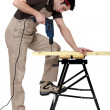 Carpenter drill through plank of wood - Stock Photo