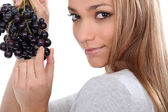 A young woman savouring sensually a grape — Stock Photo