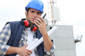 Tradesman speaking into a walkie talkie — Stock Photo