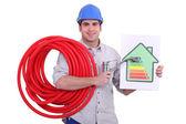 Plomero sosteniendo un grifo y una etiqueta de consumo de energía — Foto de Stock