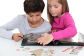 Children looking at a stamp album — Stock Photo
