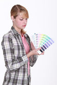 Woman holding up paint samples — Stock Photo
