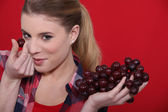 Woman holding bunch of red grapes — Stock Photo