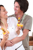 Couple in kitchen holding dessert — Stock Photo