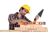 A mason using a level to check his wall. — Stock Photo