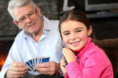 Young girl playing cards with grandpa — Stock Photo