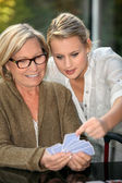 Grandmother and granddaughter playing cards — Stock Photo